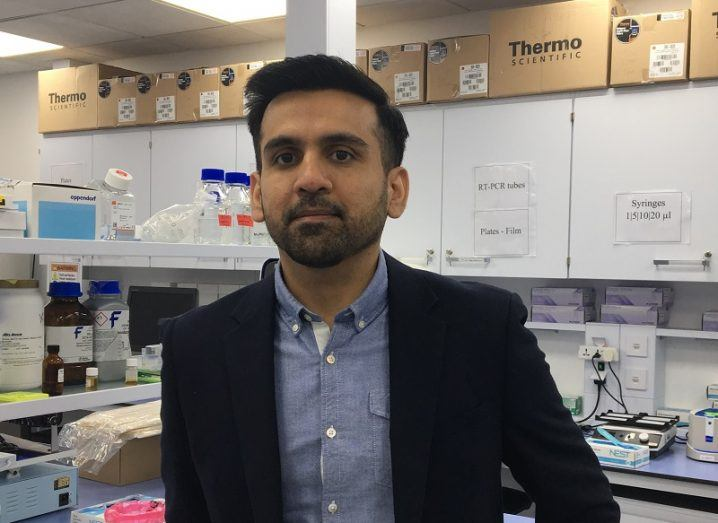 Omar Khan standing in his lab in a dark blazer and blue shirt.