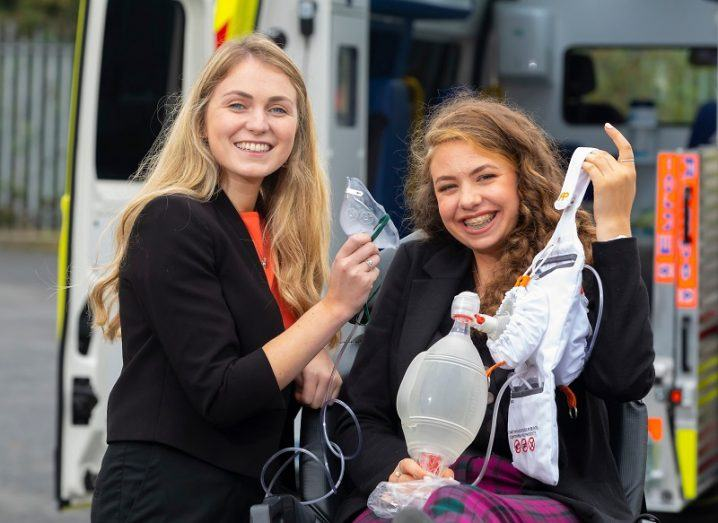 Máire Kane and Hannah Grogan smiling while holding their invention beside an ambulance.
