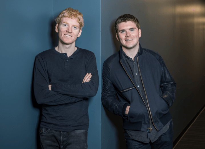 Stripe's founders, the Collison brothers, standing in front of a dark blue wall. One has red hair and a navy long-sleeved shirt on, with his arms crossed. The other has brown hair and a navy jacket, with his hands in his pockets.