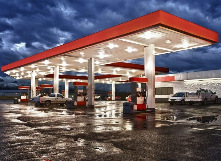 A red and white petrol station lit up by lights on a dark, cloudy night.