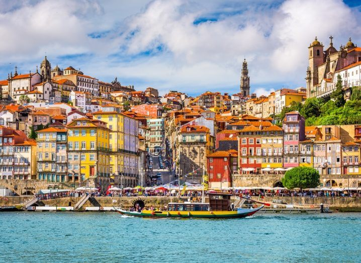 Porto old town skyline from across the Douro River with multi-coloured buildings.