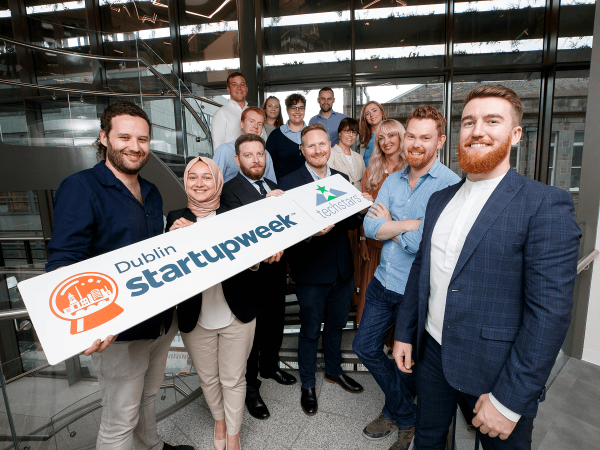 """Fourteen entrepreneurs stand in a glass office hallway, holding a large sign that says """"Dublin Startup Week""""."""
