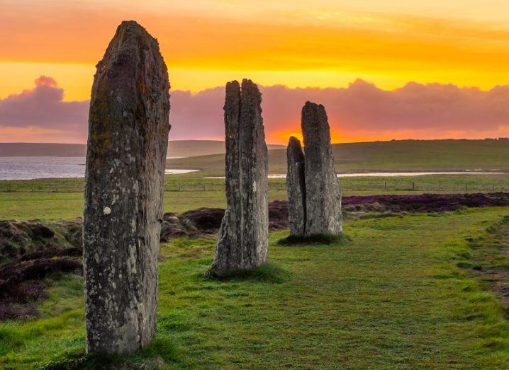 Three ancient standing stones on the Shetland Islands against a yellow dusk sky.