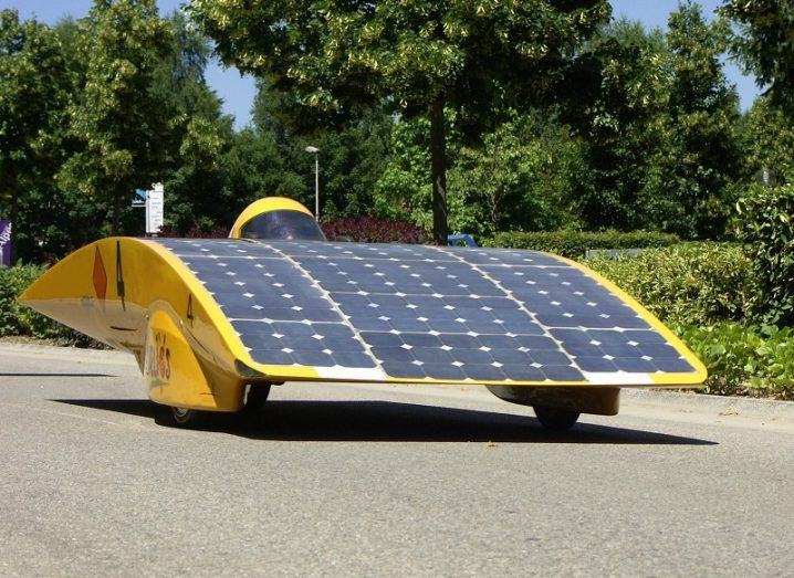 Yellow experimental car covered in solar panels with trees in the background.