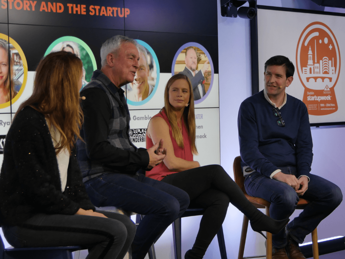 """A group of two women and two men sitting on stools in front of a large TV screen which says """"The Story and the Startup""""."""