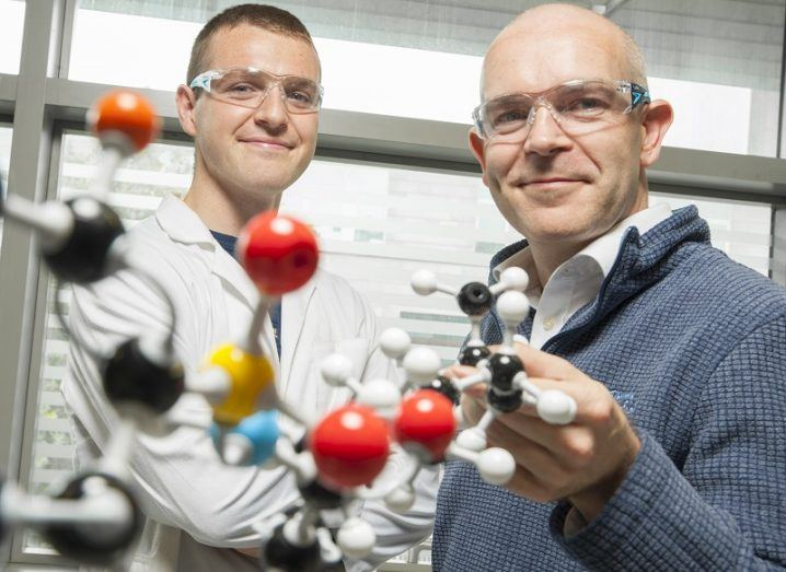 Conor Horgan and Tim O'Sullivan smiling and wearing safety glasses in front of a molecule model.