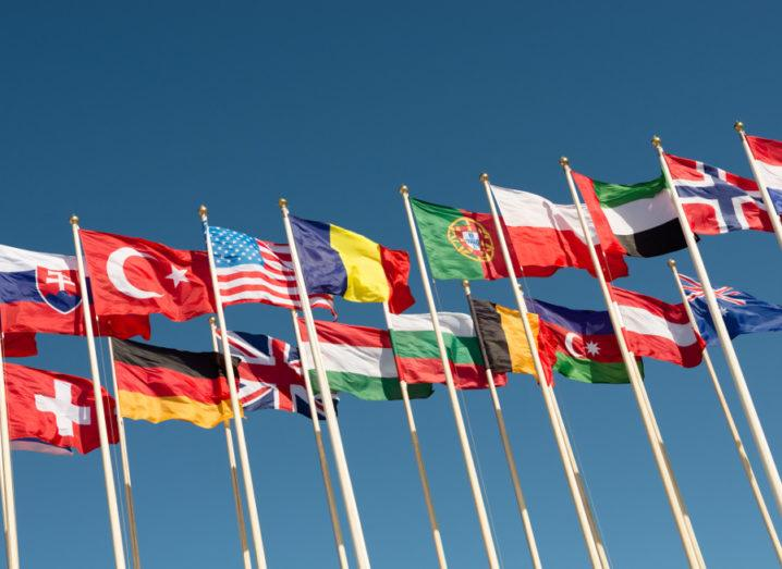 Flags of different countries on flagpoles fluttering in the wind.