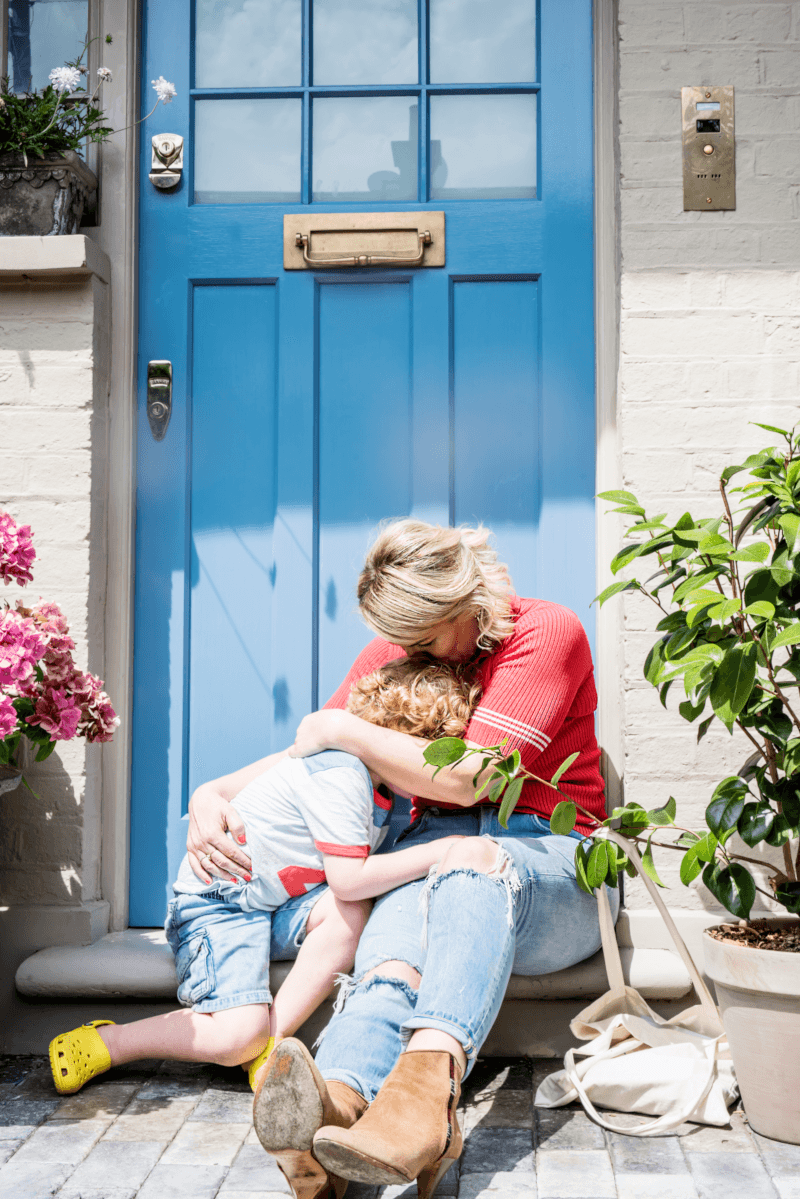 A mother and child cuddle each other on the front step of a house with a teal door. The mother is wearing a red t-shirt and blue jeans with brown boots, and the child is wearing a grey t-shirt, jeans and yellow Crocs.