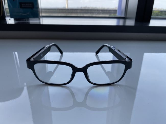 A pair of smart glasses with black frames pictured on a clean surface.
