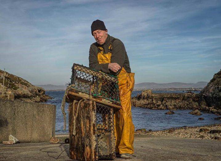 A fisherman stands leaning on a fishing cage against a scenic backdrop against the sea on Arranmore, an island off the coast of Donegal.