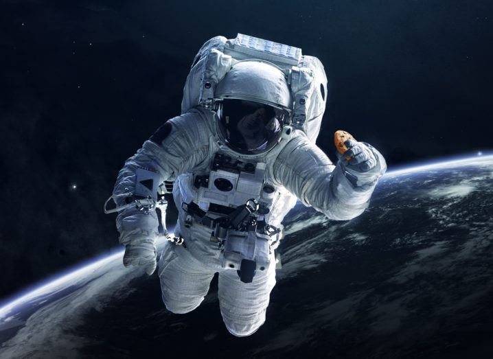 An astronaut floating in space above the Earth in an EVA suit, holding a chocolate chip cookie in their left hand.