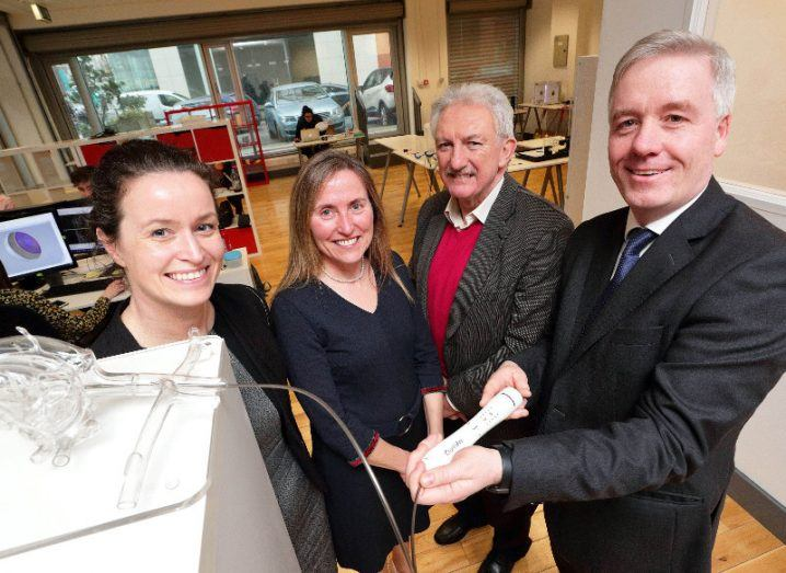 Two women and two men in an office demonstrating a new medical device for heart disease treatment.