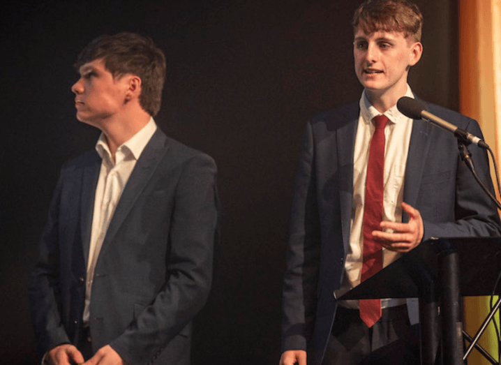 Two young men stand on a stage in dark suits and white shirts.