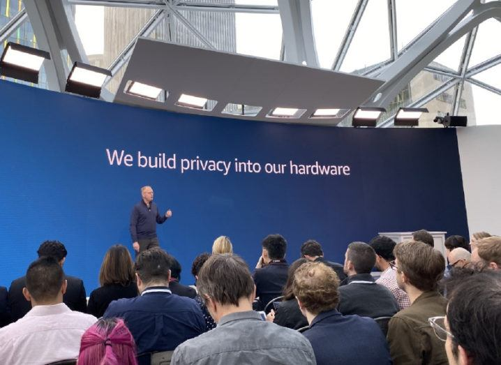 "A man speaks to an audience gathered at Amazon's Seattle headquarters in front of a backdrop that says: ""We build privacy into our hardware""."