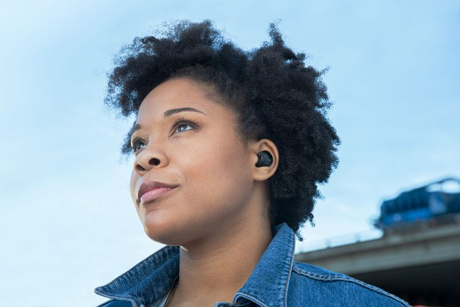 A woman in a denim shirt pictured wearing the black Echo Buds in her ears.