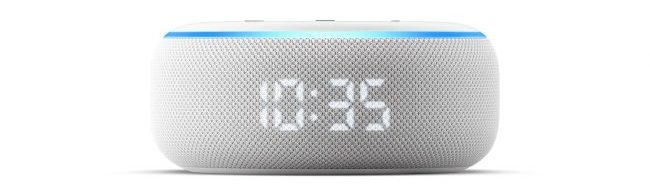 A round white device lit up by a blue light around the rim, with a clock displaying 10.35 on the speaker surface.