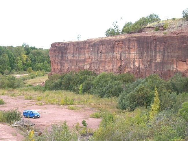 Shot of a cliff with different sediment layers with a small, blue truck nearby.