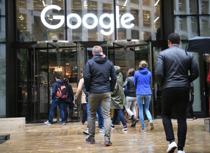 View of people walking into building with glass facade and Google logo above the door on a wet day.