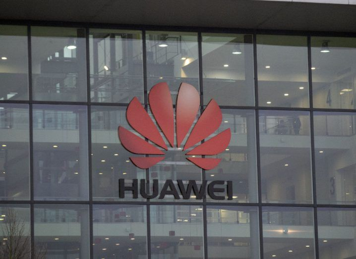 View of red lotus Huawei logo on glass building facade.