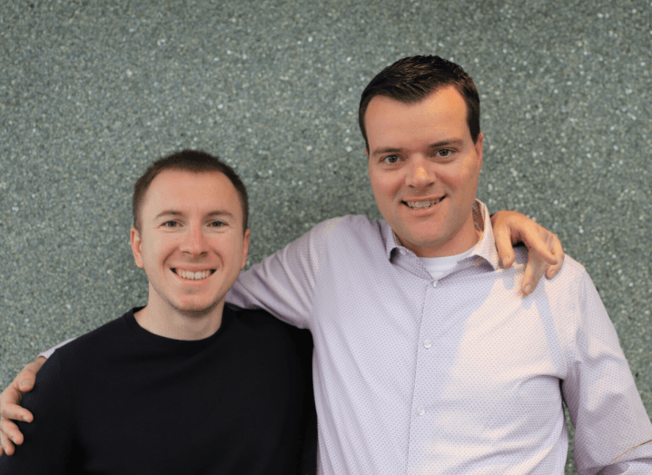 Two GitLab founders stand beside one another in front of a grey wall. One is taller and wearing a pink shirt, the other is wearing a grey jumper. Both have dark hair and are smiling.