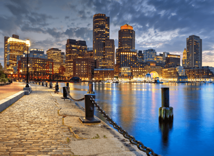 Skyscrapers in front of a body of water in Boston at night time.