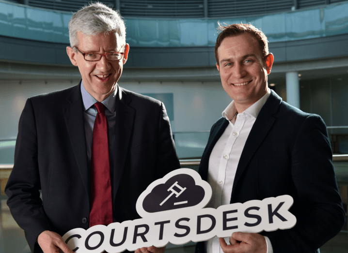 A man with grey hair and glasses wearing a black suit, white shirt and red tie holds a sign that says Courtsdesk. To the right of him, a man with brown hair wearing a black blazer and a white shirt with the collar unbuttoned holds the other side of the sign.