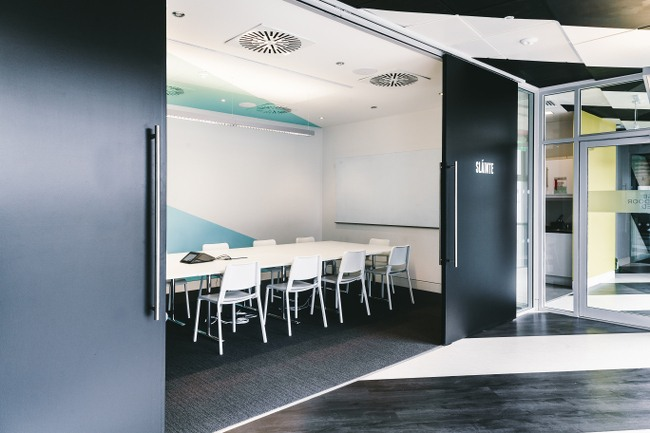 Two moving walls slide apart to show a boardroom inside with a long white table surrounded by white chairs