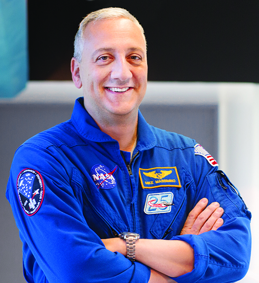 A smiling silver-haired man in a blue astronaut flight suit bearing NASA's insignia stands with his arms folded, looking at the camera.