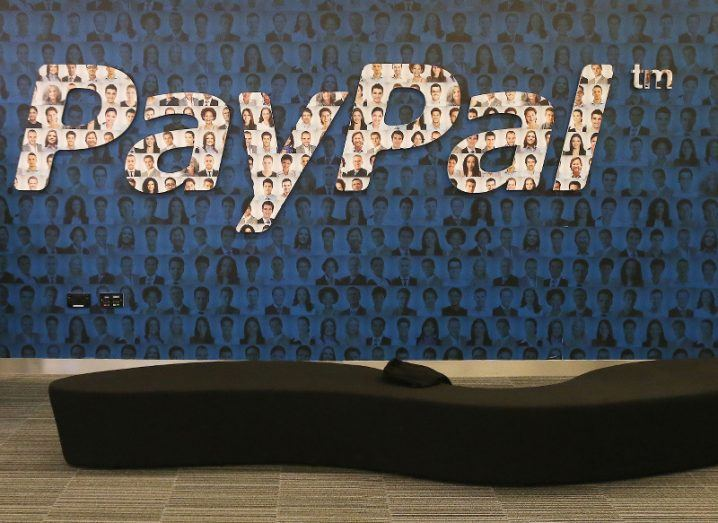 A dark blue office wall with a large white PayPal logo, all of which are covered with different faces.