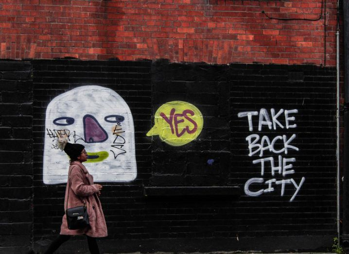 A woman in a wool coat and hat walks past a brick wall graffitied with a cartoonish face saying 'yes' and the words 'take back the city' written beside it.