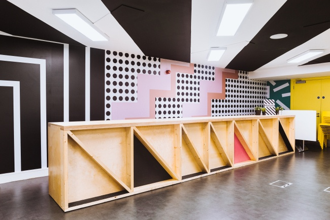 A brightly coloured room (black, white and pink) with a wooden fold-away stage.