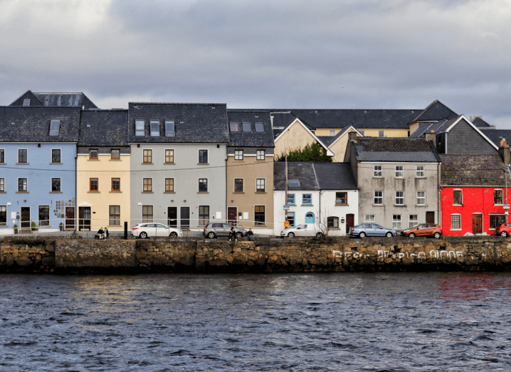 Colourful buildings in front of a body of water at Galway Harbour.