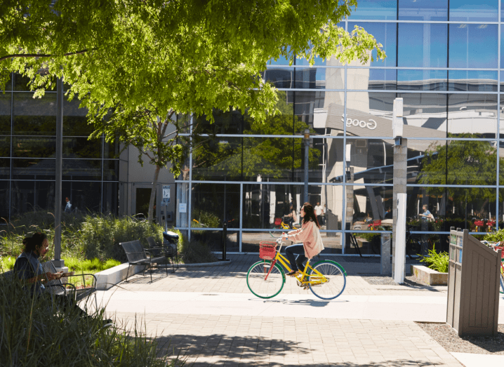 A woman on a colourful bike cycles past a large, glass office building. Outside the building it's sunny and there are big leafy trees planted. A man is sitting under one of the trees reading.