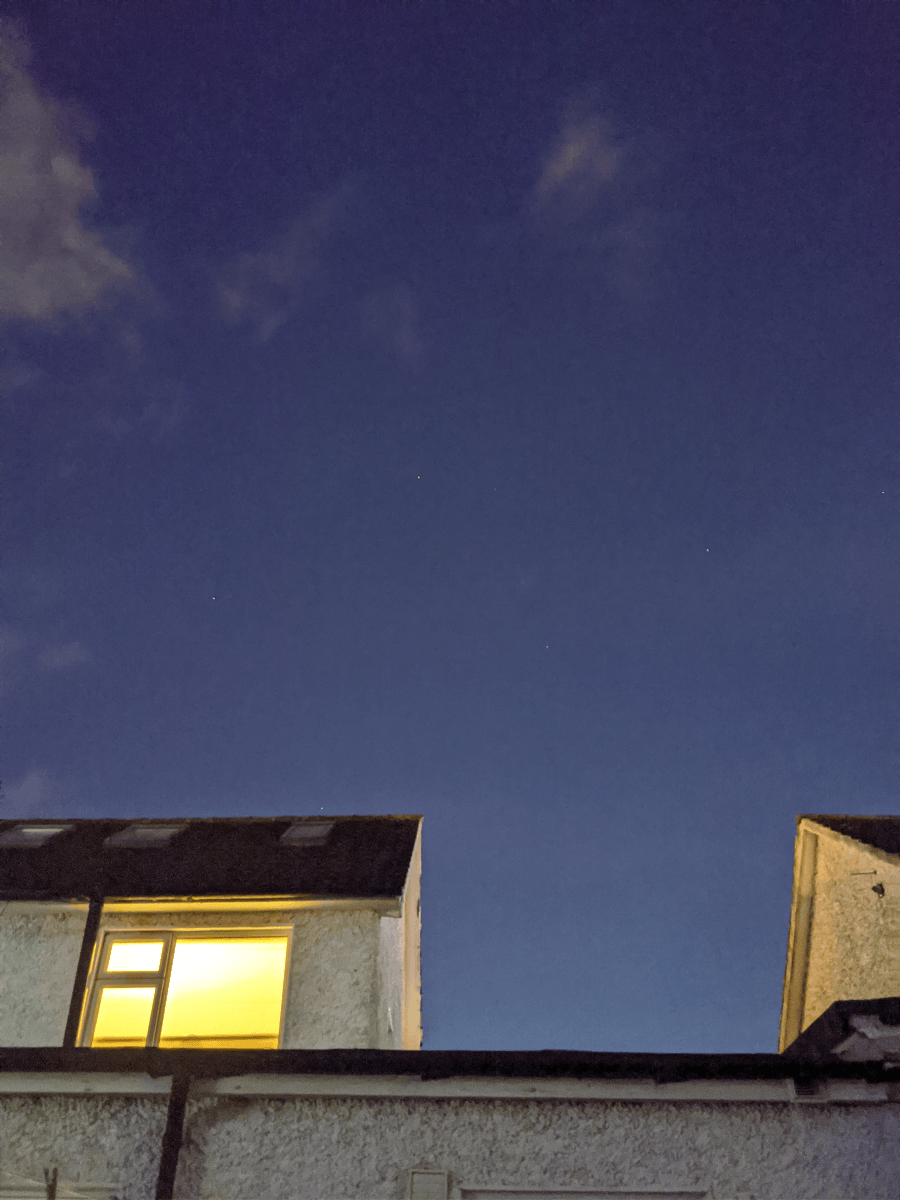 A photograph of a white house, with black roof tiles, three attic windows and a black drain pipe running down it under a blue night sky. There are clouds above it, as well as a few stars dotted around.