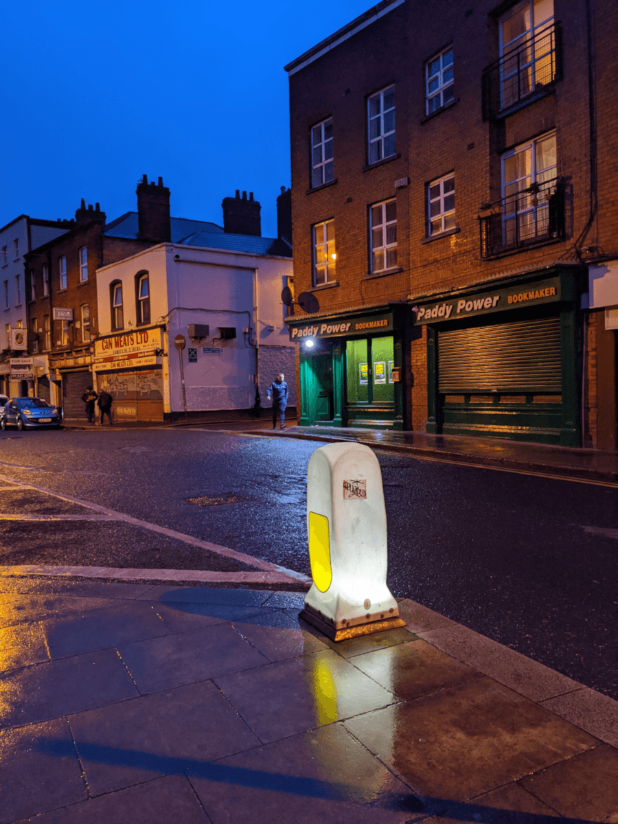 An illuminated traffic bollard on the pavement, across the road from a Paddy Power bookmakers and a butcher's shop.