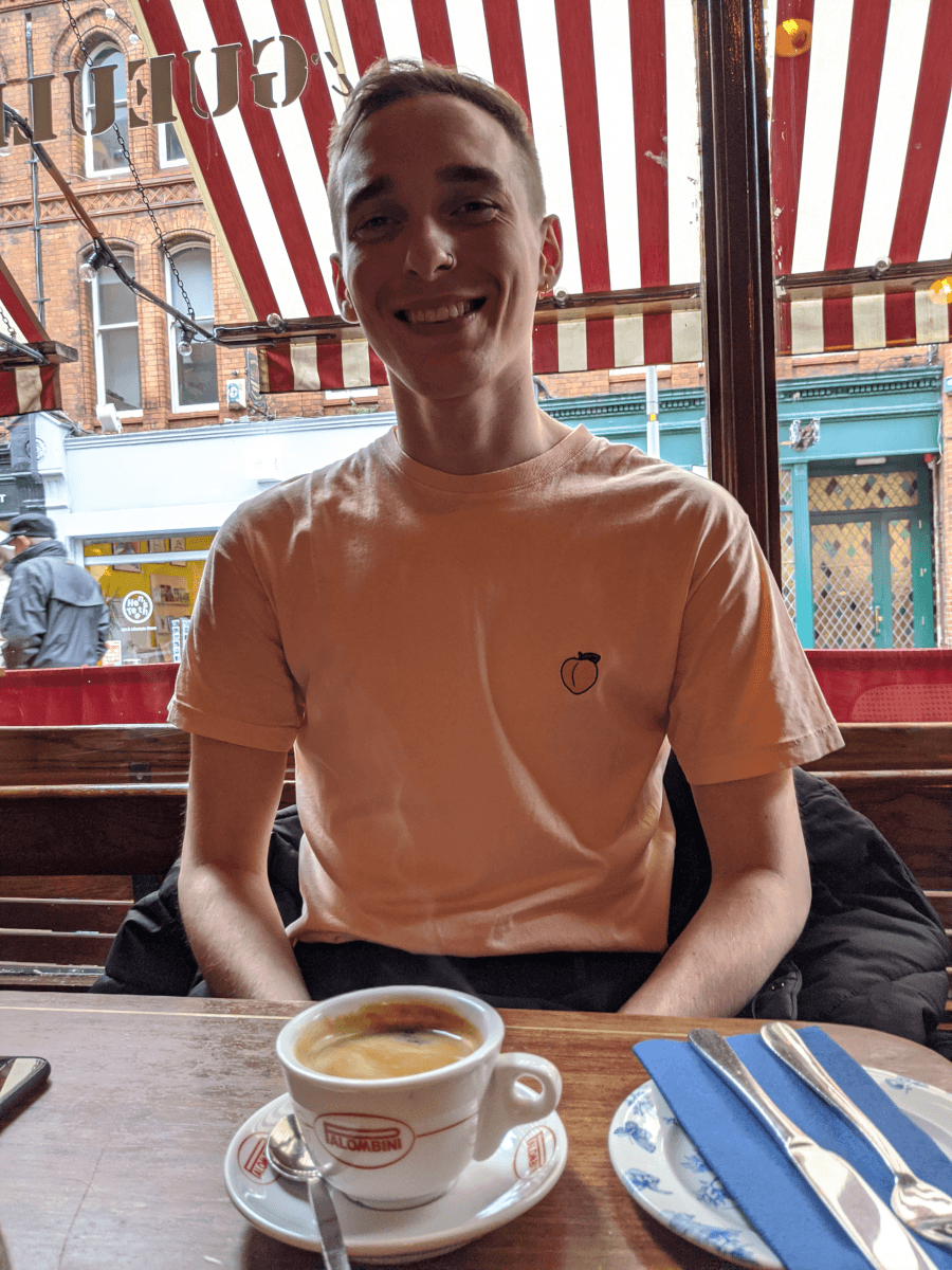 A young man with brown hair sits in a café drinking a coffee. He is wearing a pink t-shirt with a cartoon peach on it.