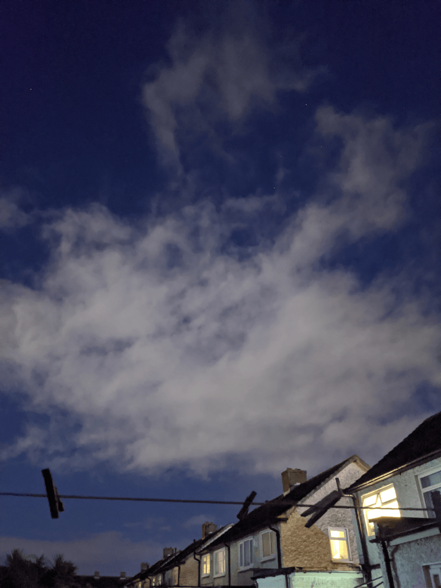 Clouds in a blue night sky over a row of white houses. Across the foreground of the photograph, there is a washing line with pegs on it.