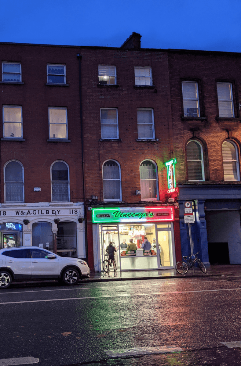 A red brick Georgian building with a chip shop on the ground floor. Above the door and windows of the restaurant, there is a neon sign that reads Vincenzo's. There are young boys on bikes in the doorway to the takeaway.