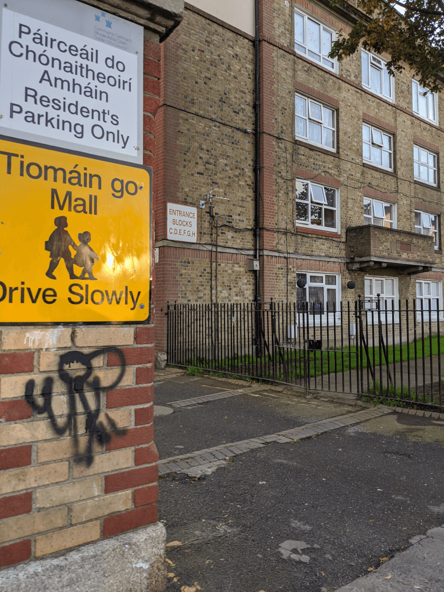 A yellow sign outside a block of flats with yellow bricks. The sign says Tiomáin go Mall, which means Drive Slowly.