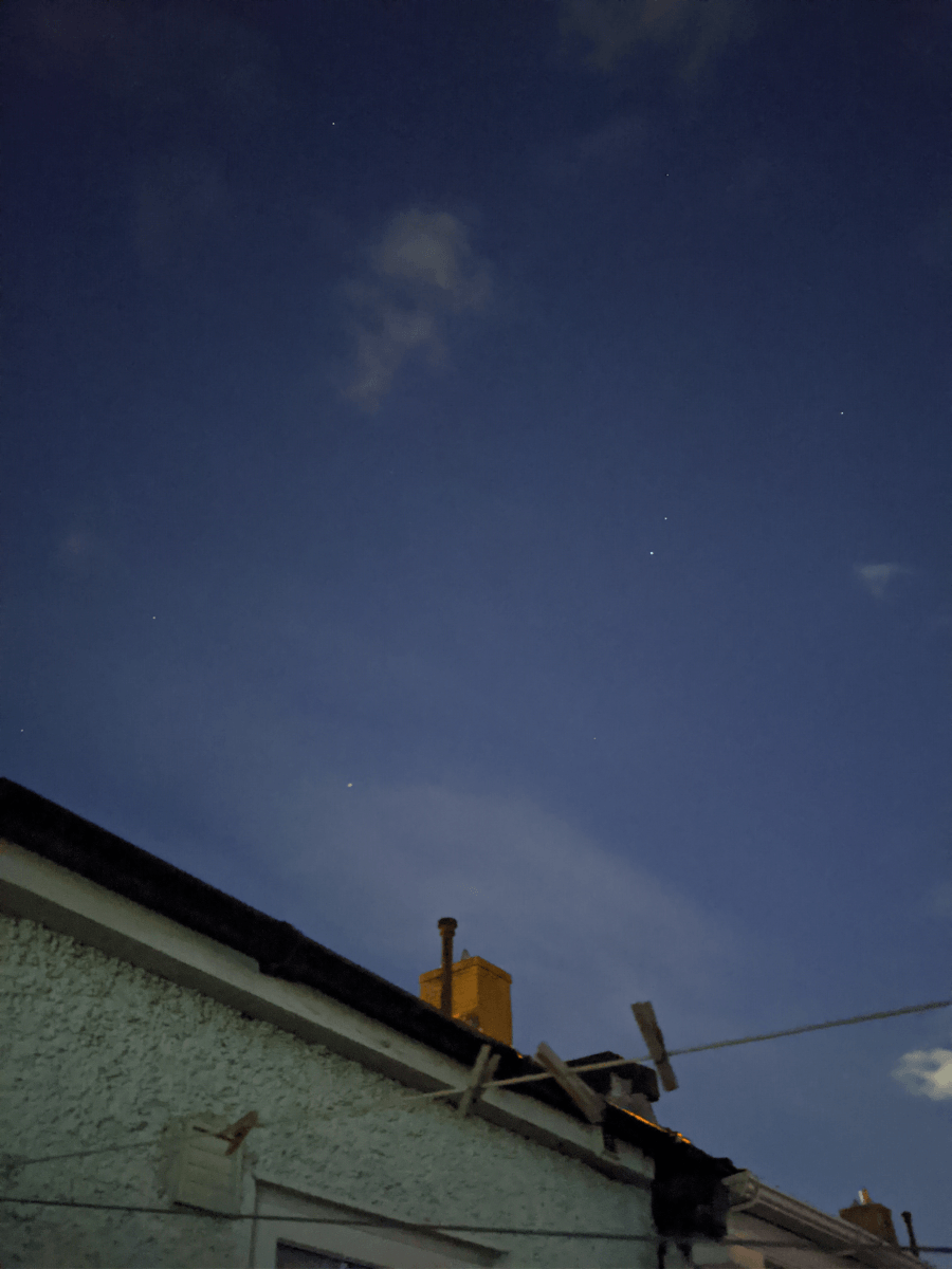 A gutter and a washing line underneath a blue night sky with stars dotted around it.
