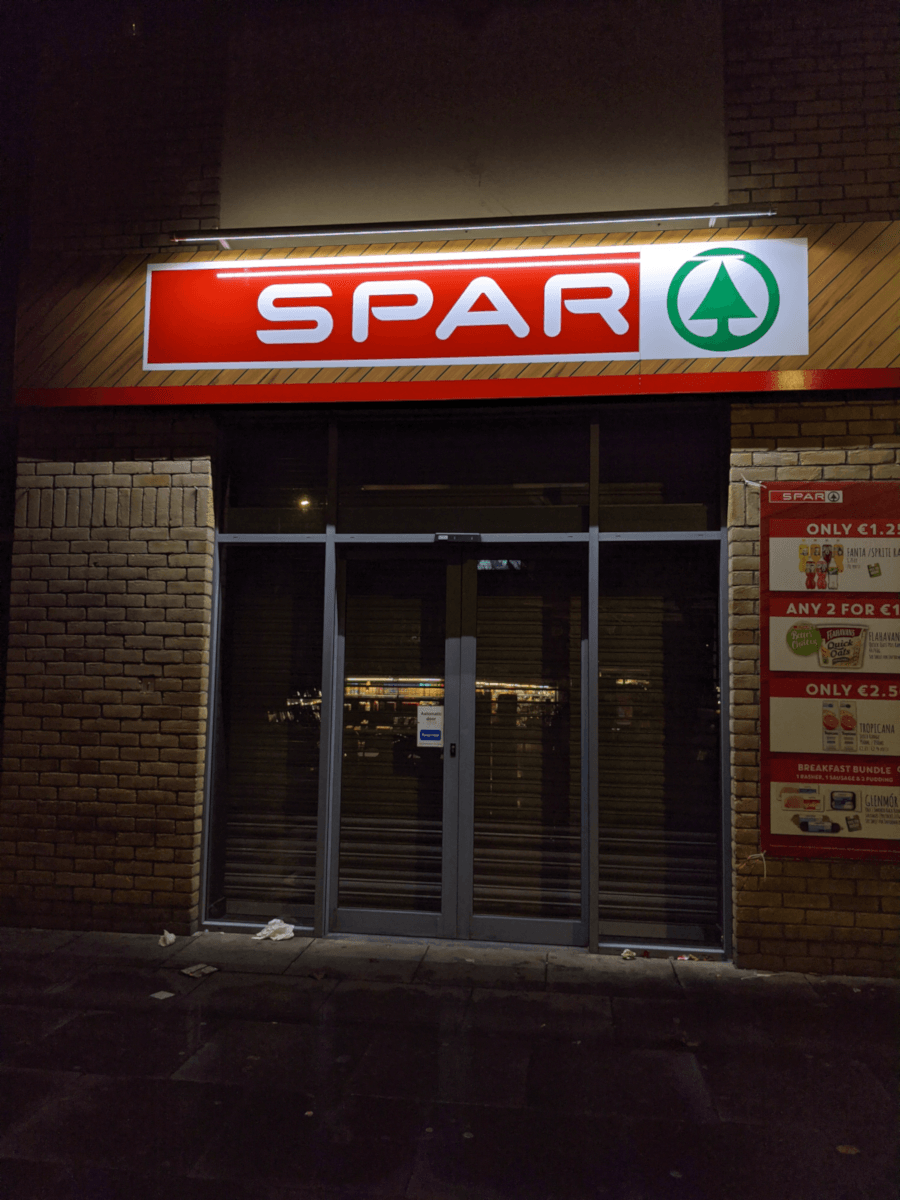 "The exterior of a Spar supermarket at night time. It has yellow bricks on the walls outside and a glass front door with the shutter pulled down. The word ""Spar"" is illuminated on the shopfront."
