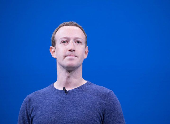 View of Mark Zuckerberg in blue sweater standing against blue background.