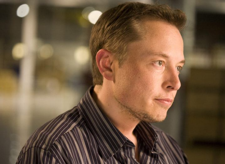 Elon Musk, Tesla CEO, looking off into the distance wearing striped shirt.