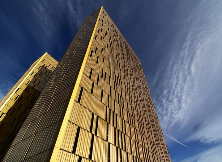 View of gold façade of European Court of Justice building taken from below on a bright day.