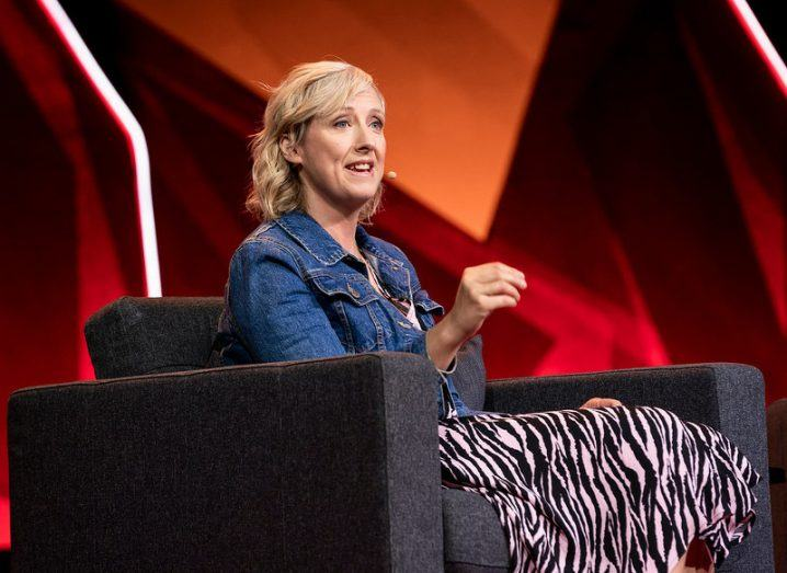 A woman seated on a stage with a red backdrop, wearing a head mic and speaking while gesturing with her hands.