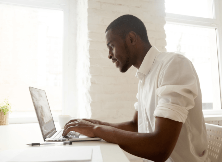 A man in a white shirt with the sleeves rolled up above his elbows types on a laptop in a white room, on a white desk.