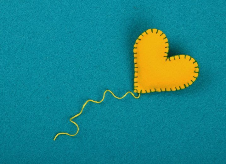A felt yellow heart stitched together with green thread, with a long yellow thread trailing from its point, on a sea-green felt background.
