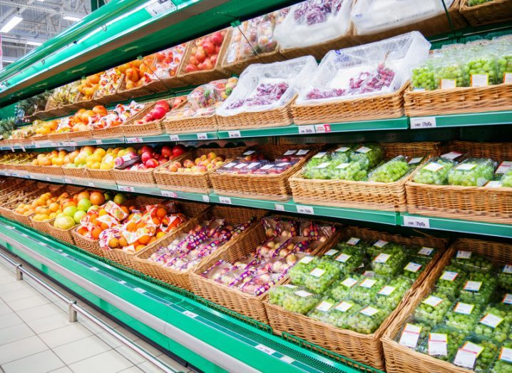 Green refrigerated shelves of a supermarket fully stocked with colourful fruit such as grapes, oranges and apples.