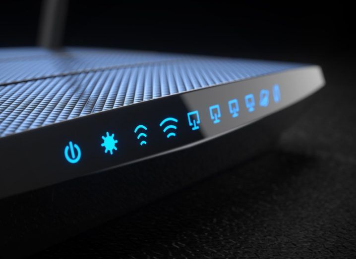 View of black wi-fi router with various blue icons illuminated.