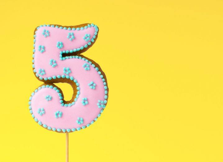 A gingerbread lollipop shaped like the number five and decorated with pink icing and tiny blue flowers.